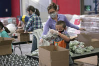 Phoenix resident Erin Pfeifer, 40, unloads boxes of bagged peas as her 8-year-old son, Dylan, places them into the boxes at St. Mary's Food Bank in Phoenix on Thursday, March 18, 2021. This was the second volunteer event Pfeifer and her son attended with the food bank. (AP Photo/Cheyanne Mumphrey)