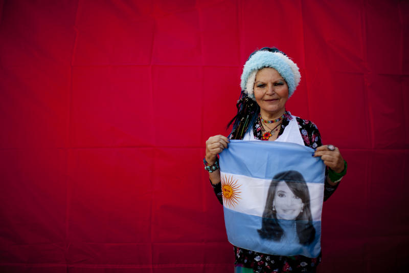 In this Oct. 3, 2018 photo, Yenni Prieto poses for a photo holding an Argentine national flag designed with an image of former President Cristina Fernandez, during a demonstration demanding improved conditions for disabled retirees, in Buenos Aires, Argentina. A battery of corruption allegations and criminal charges against former President Cristina Fernandez hasn't fazed a strong band of hard-core backers including Prieto, who have helped make her a leading, if undeclared, contender to regain power in next year's elections. (AP Photo/Natacha Pisarenko)