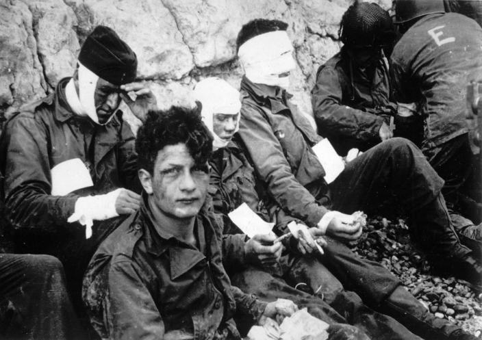 Men of the American assault troops of the 16th Infantry Regiment, injured while storming a coastal area code-named Omaha Beach during the Allied invasion of Normandy, France, wait by the chalk cliffs at Colleville-sur-Mer for evacuation to a field hospital for further treatment on June 6, 1944. (Photo: AP)