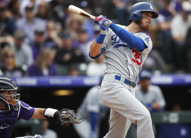 Los Angeles Dodgers' Cody Bellinger, right, follows the flight of his three-run home run off Colorado Rockies starting pitcher Tyler Anderson in the fifth inning of a baseball game Friday, April 5, 2019, in Denver. (AP Photo/David Zalubowski)
