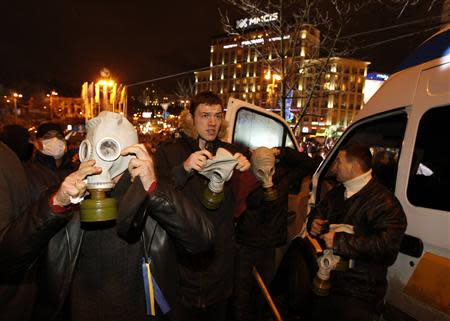 Protesters wear gas masks during a meeting to support EU integration at European square in Kiev