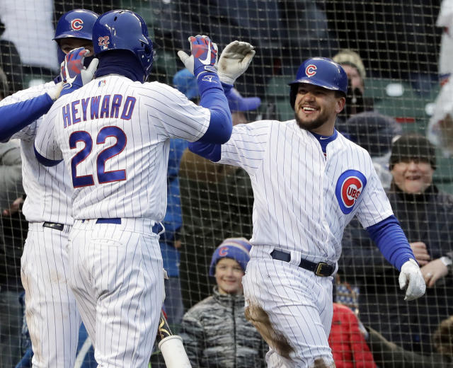 Cubs' runners Kyle Schwarber (right) and Jason Heyward celebrate after scoring on the same wild pitch during Saturday's wild win against the Braves. (AP)