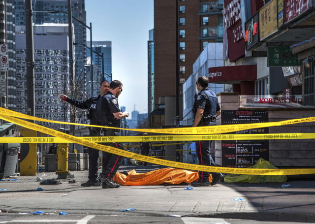 <p>Police officers stand by a covered body in Toronto after a van mounted a sidewalk and crashed into a crowd of pedestrians on Monday, April 23, 2018. (Photo: Aaron Vincent Elkaim/The Canadian Press via AP) </p>