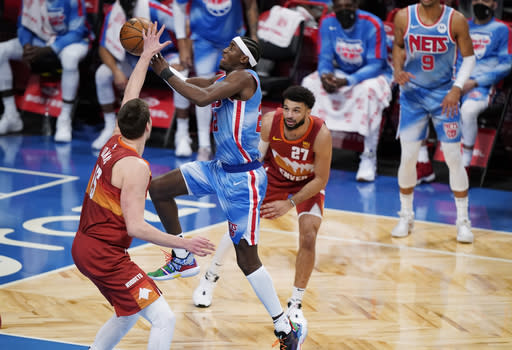 Brooklyn Nets guard Caris LeVert (22) goes for a layup as Denver Nuggets center Nikola Jokic (15) and guard Jamal Murray (27) defend during the second quarter of an NBA basketball game Tuesday, Jan. 12, 2021, in New York. (AP Photo/Kathy Willens)