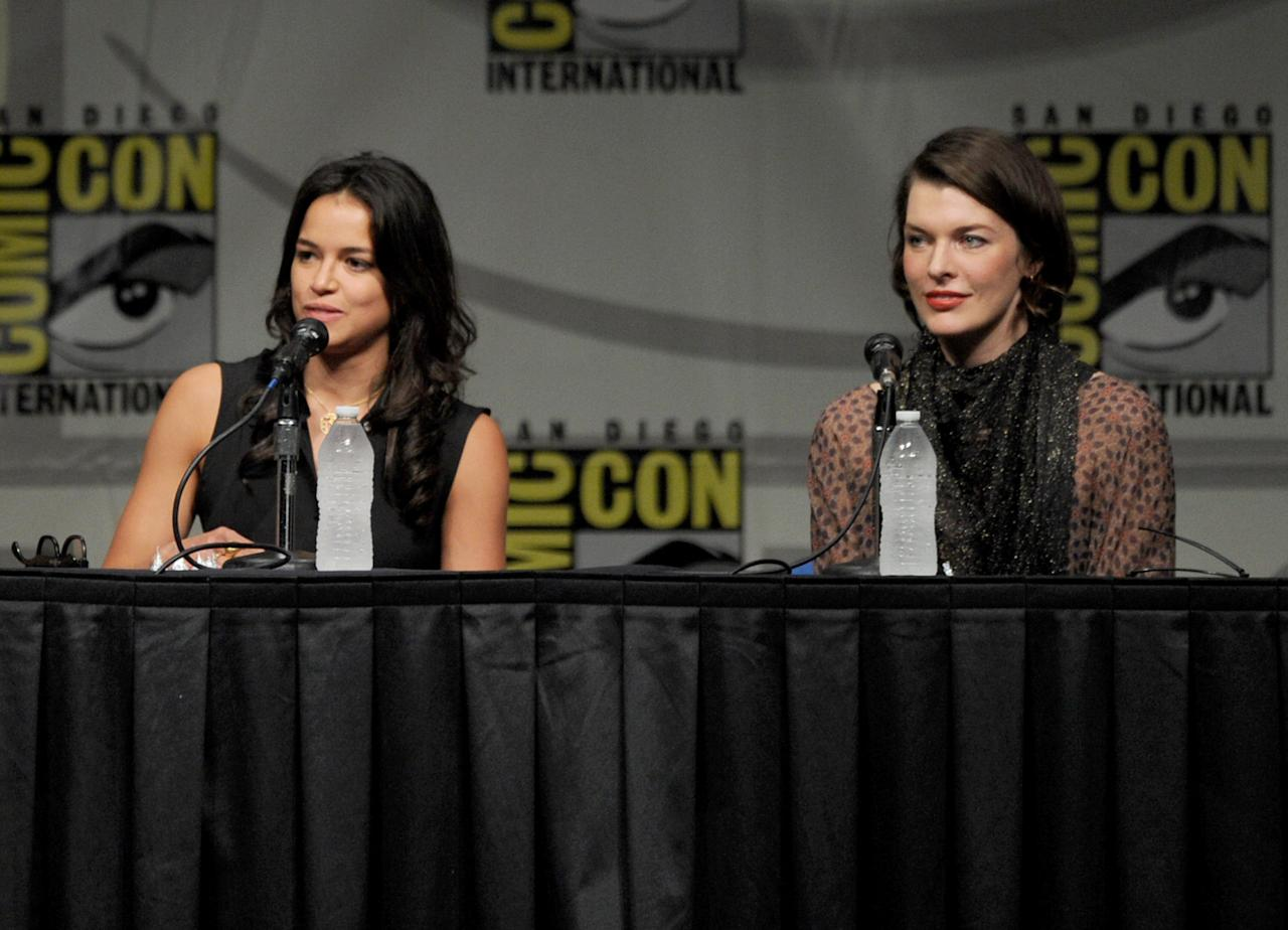 "SAN DIEGO, CA - JULY 13:  Actresses Michelle Rodriguez (L) and Milla Jovovich speak at the Screen Gems' ""Resident Evil: Retribution"" panel during Comic-Con International 2012 at San Diego Convention Center on July 13, 2012 in San Diego, California.  (Photo by Kevin Winter/Getty Images)"