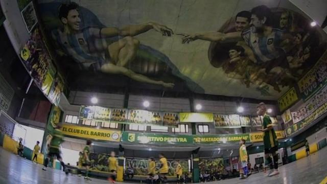 "Representing God and Adam from the famous Michelangelo Sistine Chapel painting, Diego Maradona and Lionel Messi look down from above on a futsal pitch in Argentina. The artwork, a sporty version of ""Creation of Adam"", has turned the headquarters of the small team into the Sistine Chapel of Argentine football."