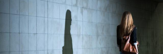 Woman walking, her shadow cast on the wall.