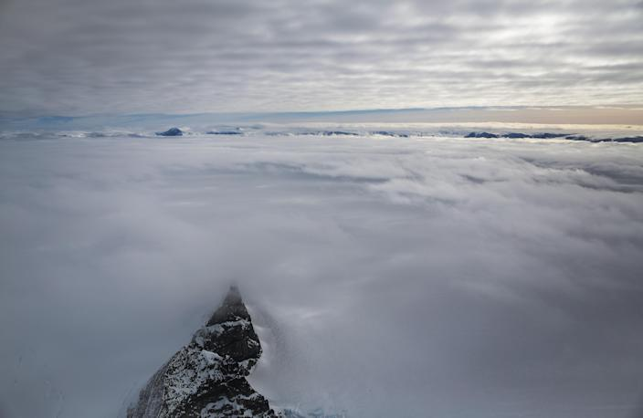 <p>A mountain (bottom left) peeks through clouds and ice as seen from NASA's Operation IceBridge research aircraft, near the coast of the Antarctic Peninsula region on Oct. 31, 2017, above Antarctica. (Photo: Mario Tama/Getty Images) </p>