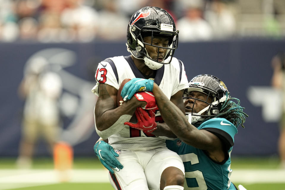 Houston Texans wide receiver Brandin Cooks (13) catches a pass for a first down as Jacksonville Jaguars cornerback Shaquill Griffin (26) defends during the first half of an NFL football game Sunday, Sept. 12, 2021, in Houston. (AP Photo/Sam Craft)