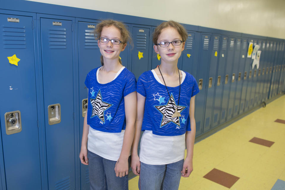 In this June 6, 2013 photo, Finja Scholz, left, and her twin sister, Alina, one of the 24 sets of twins from Highcrest Middle School in Wilmette, Ill., pose for a portrait in Wilmette, Ill. The group is attempting to break a Guinness Book of World Records for the amount of twins in one grade which is currently 16 sets. (AP Photo/Scott Eisen)