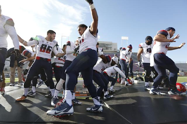 Arizona senior football players try to regain their balance after the flooring of the stage gives way as they celebrate their beating Boston College, 42-19, in the AdvoCare V100 Bowl NCAA college football game, Tuesday, Dec. 31, 2013, by dancing on the stage at Independence Stadium in Shreveport, La. (AP Photo/Rogelio V. Solis)