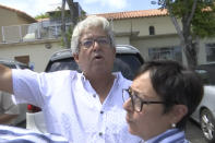 """In this Sunday, June 27, 2021 image from video, Alfredo Lopez talks about how his family escaped from the Champlain Towers South condo building in Surfside, Fla. Lopez and his wife, Marian, right, were asleep when the first thundering blast jolted them awake. Alfredo rushed to wake his 24-year-old son, Michael. When Alfredo opened the front door that night, half of the building was gone. A jagged five-foot chunk of flooring barely left enough room to escape. """"There was no hallway, no ceiling, no apartments, no walls, nothing."""" The 61-year-old froze in terror, unable to move. """"I was petrified. I really thought, 'This is it. We are going to die'."""" (AP Photo/Stacey Plaisance)"""