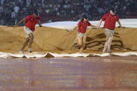 Fenway Park grounds crew pull a tarp into place on the infield during a rain delay in the fifth inning of a baseball game between the Boston Red Sox and the New York Yankees, Thursday, July 22, 2021, in Boston. (AP Photo/Elise Amendola)