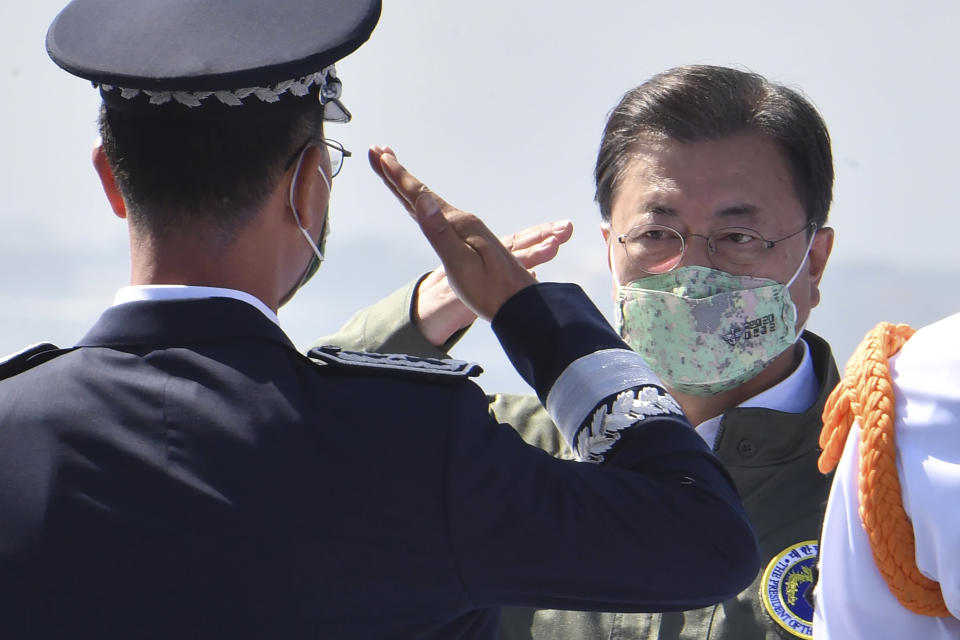 South Korean President Moon Jae-in, right, salutes during the 73rd anniversary of Armed Forces Day on the landing platform helicopter (LPH) ship Marado in Pohang, South Korea Friday, Oct. 1, 2021. (Song Kyung-Seok/Pool Photo via AP)
