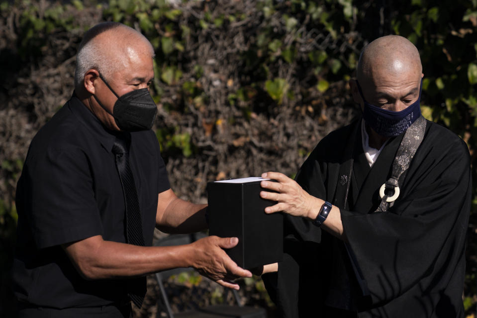 Clyde Matsumura, left, hands a small box containing the ashes of his grandfather, Giichi Matsumura, to Shumyo Kojima, a head priest of Zenshuji Buddhist Temple, during a memorial service at Woodlawn Cemetery in Santa Monica, Calif., Monday, Dec. 21, 2020. Giichi Matsumura, who died in the Sierra Nevada on a fishing trip while he was at the Japanese internment camp at Manzanar, was reburied in the same plot with his wife 75 years later after his remains were unearthed from a mountainside grave. (AP Photo/Jae C. Hong)