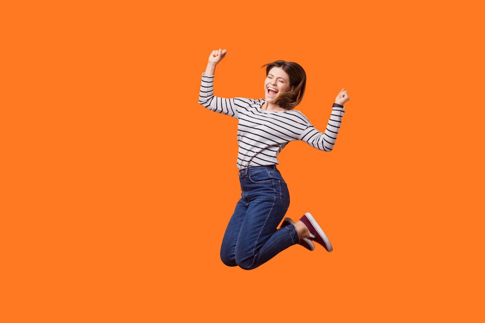 Excited woman with brown hair in casual shirt and denim jumping celebrating victory.