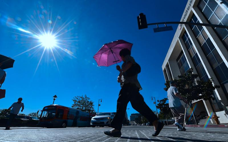 A pedestrian uses an umbrella as a heat shield in Los Angeles on Tuesday, when temperatures climbed past 100 downtown.