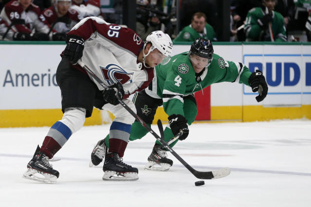 Colorado Avalanche left wing Andre Burakovsky (95) tries to get the puck past Dallas Stars defenseman Miro Heiskanen (4) during the first period of an NHL hockey game in Dallas, Saturday, Dec. 28, 2019. (AP Photo/Michael Ainsworth)