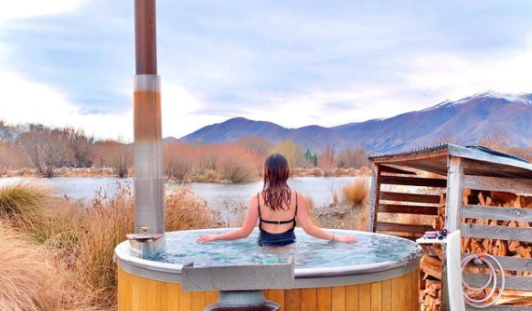 A woman sits in a hot tub and looks at a mountainous New Zealand landscape.