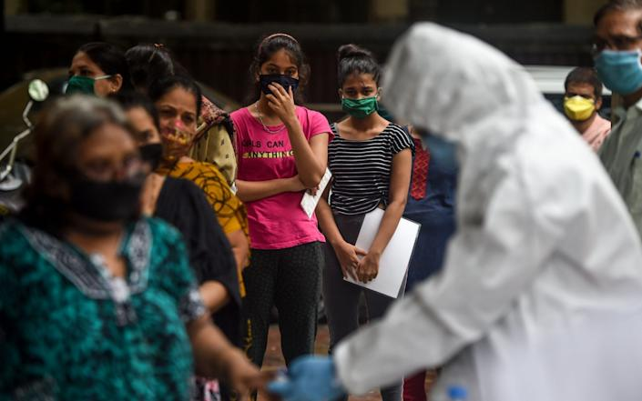 Residents queue up to get tested for the virus near residential buildings in Mumbai, India, where it's expected cases will surpass one million in the next 24 hours - AFP