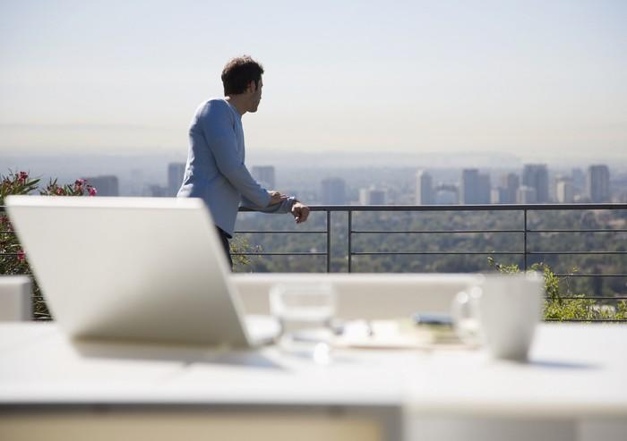 A man looking out at a city on a rooftop with a table and laptop in the foreground.