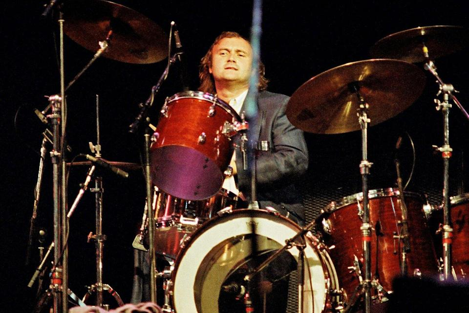 Phil Collins plays the drums on stage at Wembley Arena
