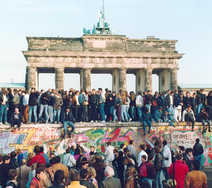 Germans from East and West stand on the Berlin Wall in front of the Brandenburg Gate on Nov. 10, 1989, one day after the Berlin Wall opened.