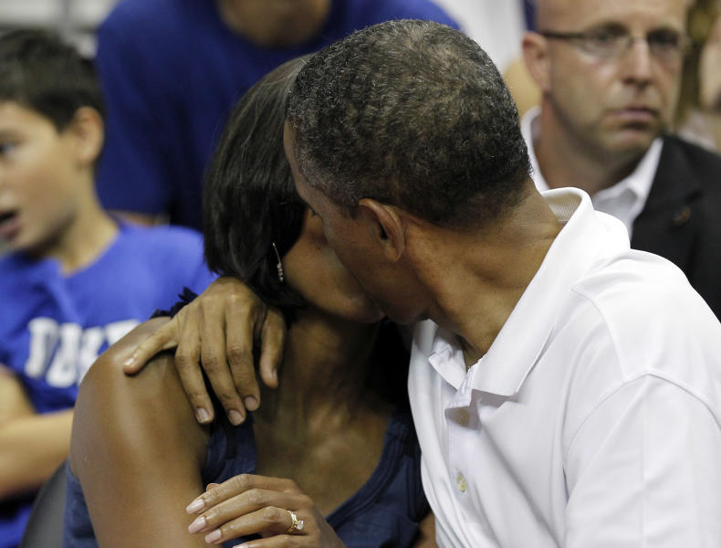 President Barack Obama, right, kisses first lady Michelle Obama for the 'Kiss Cam' while attending the Olympic men's exhibition basketball game between Team USA and Brazil, Monday, July 16, 2012, in Washington. Team USA won 80-69. (AP Photo/Alex Brandon)