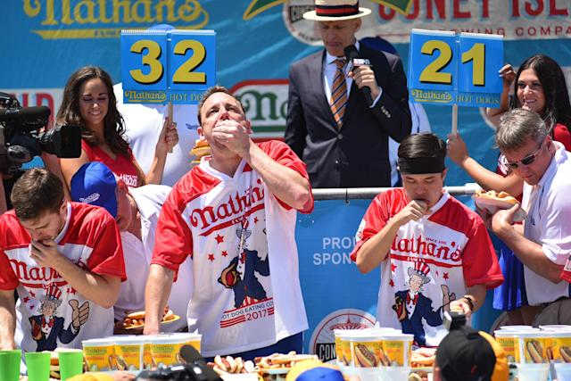 <p>Joey Chestnut, center, at the Nathan's Famous International Hot Dog Eating Contest at Coney Island in Brooklyn, New York City, U.S., July 4, 2017. (Erik Pendzich/REX/Shutterstock) </p>