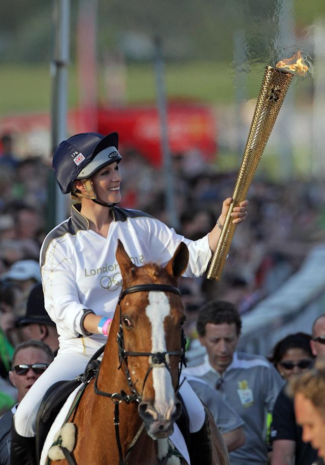 CHELTENHAM, ENGLAND - MAY 23: Olympic torchbearer Zara Phillips arrives on her horse Toy Town as she brings Olympic flame to Cheltenham Racecourse on May 23, 2012 in Cheltenham, England. The Olympic Flame arrived in the UK last Friday and is now on day five of a 70-day relay involving 8,000 torchbearers covering 8,000 miles. (Photo by Matt Cardy/Getty Images)