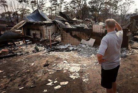 Local resident Colin Smith looks at the remains of his family's house after it was destroyed by a bushfire in the Blue Mountains suburb of Winmalee, located around 70 km west of Sydney, October 21, 2013. REUTERS/David Gray