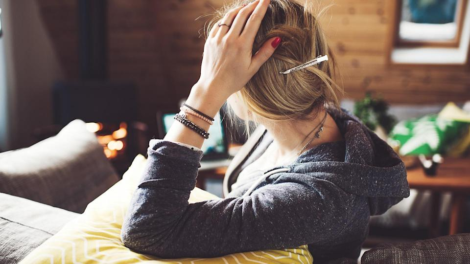 Woman at home looking away showing back of head.