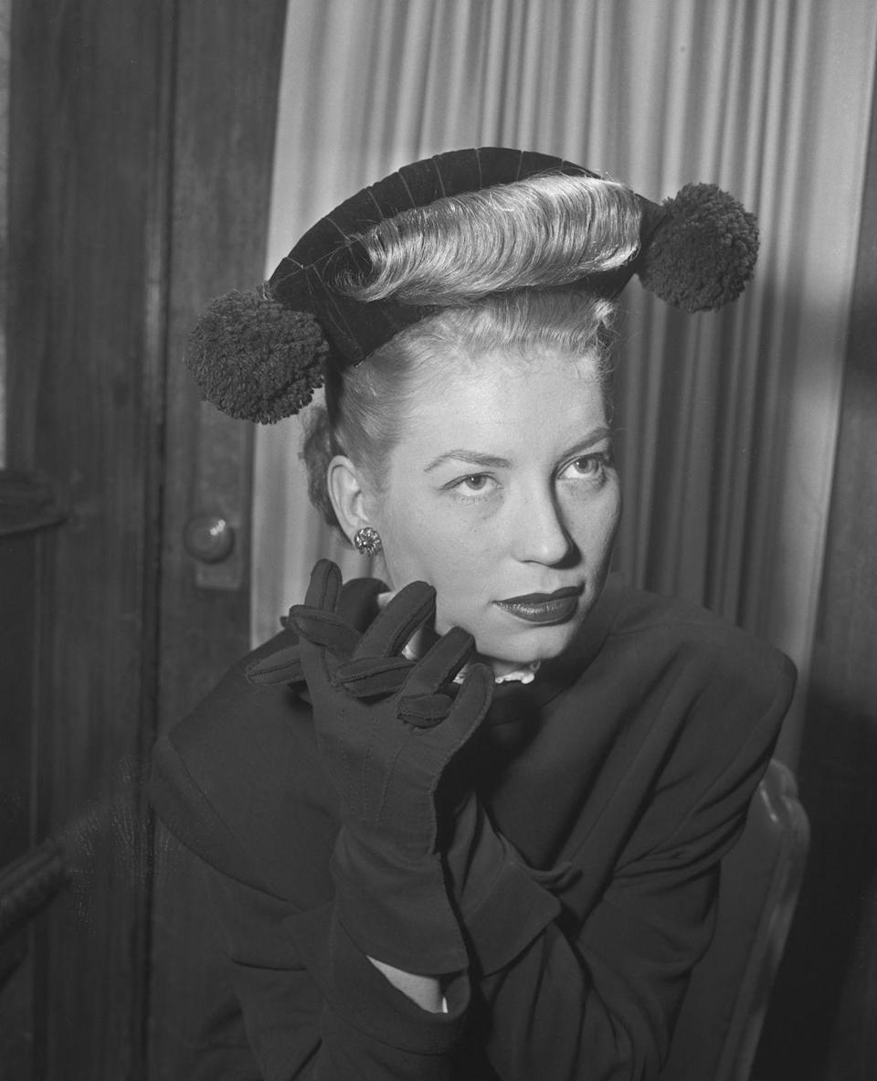 <p>Socialite Emily Brooks models the troubadour trim, where her hair is combed through her hat. The hairstyle was initially designed by London hairdresser Sidney Riche and soon became popular amongst society's elite in Europe. </p>