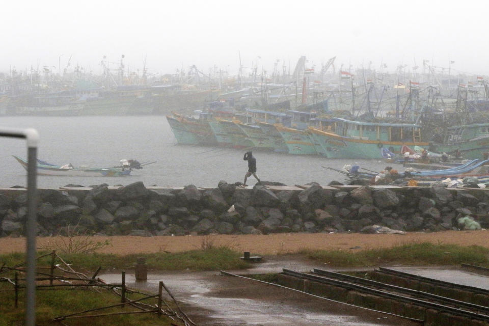 A man walks amid rain at the Kasimedu Harbor on the Bay of Bengal coast in Chennai, India, Wednesday, Nov.25, 2020. India's southern state of Tamil Nadu is bracing for Cyclone Nivar that is expected to make landfall on Wednesday. The state authorities have issued an alert and asked people living in low-lying and flood-prone areas to move to safer places. (AP Photo/R. Parthibhan)