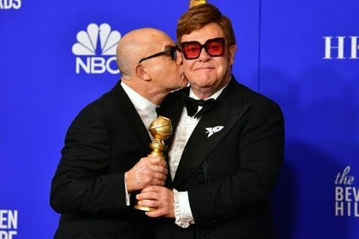 British composer Bernie Taupin (L) and British musician Elton John celebrate their long friendship and their Golden Globe win