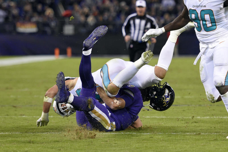 Miami Dolphins middle linebacker Kiko Alonso, top, hits Baltimore Ravens quarterback Joe Flacco. (AP)