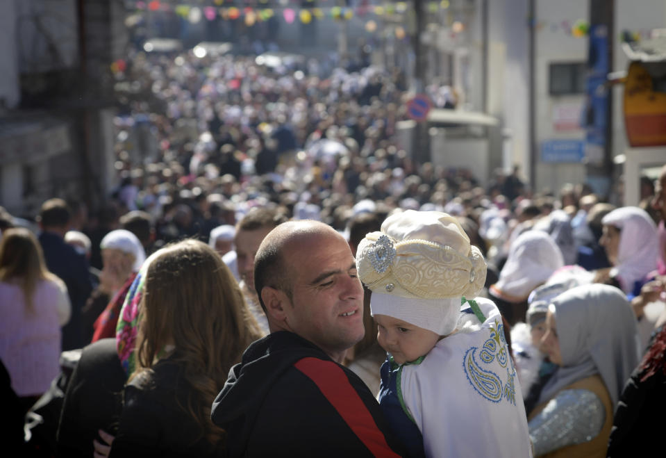 A father holds his son as they take part in a mass circumcision ceremony in the village of Ribnovo, Bulgaria, Sunday, April 11, 2021. Despite the dangers associated with COVID-19 and government calls to avoid large gatherings, Hundreds of people flocked to the tiny village of Ribnovo in southwestern Bulgaria for a four-day festival of feasting, music and the ritual of circumcision which is considered by Muslims a religious duty and essential part of a man's identity. (AP Photo/Jordan Simeonov)