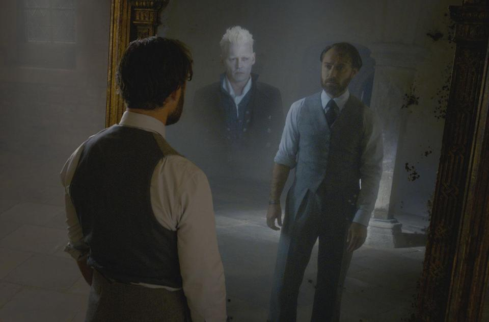 Jude Law sees his reflection and the image of Johnny Depp in a mirror in <i>Fantastic Beasts: The Crimes of Grindelwald.</i> (Photo: Warner Bros.)