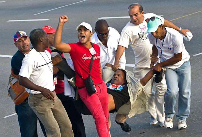 """<p>A security officer yells """"Long live Fidel! Long life Raul!"""" as he and other plain clothed security officers carry away a man who ran waving a U.S. flag moments before the start of the May Day march in Havana, Cuba, Monday, May 1, 2017. Monday's protest was a surprising breach of security at a government-organized event where agents line the route. (AP Photo/Ramon Espinosa) </p>"""