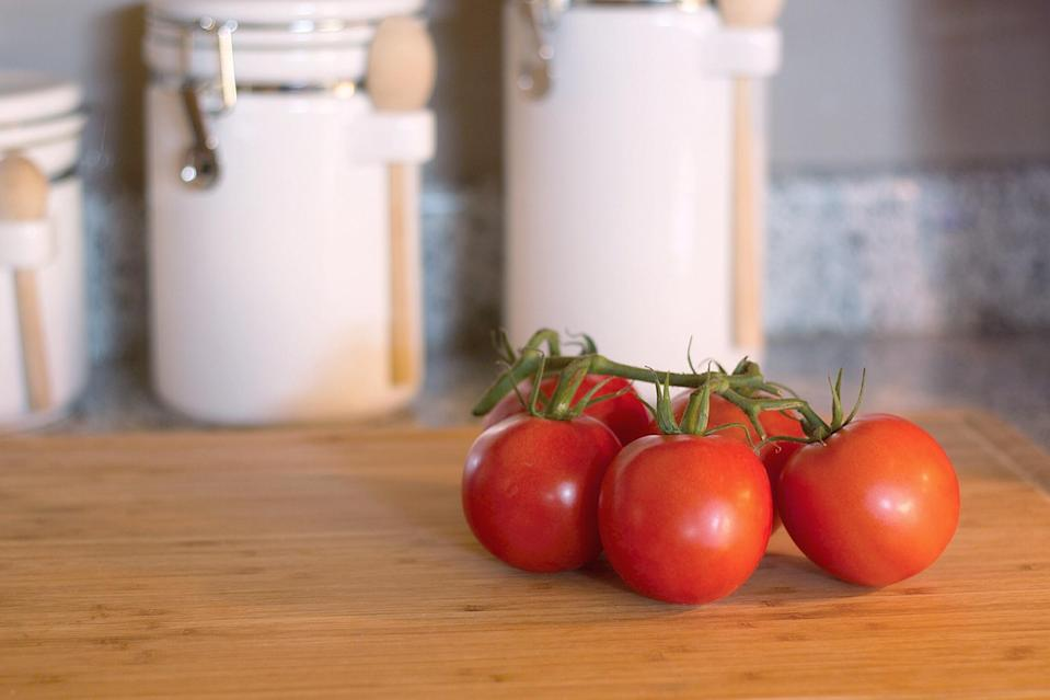 """<p>You may be tempted to keep your tomatoes in the fridge but that's doing them a massive disservice. They are actually one of those <a href=""""https://www.thedailymeal.com/healthy-eating/never-refrigerate-these-20-foods-slideshow/slide-22?referrer=yahoo&category=beauty_food&include_utm=1&utm_medium=referral&utm_source=yahoo&utm_campaign=feed"""" rel=""""nofollow noopener"""" target=""""_blank"""" data-ylk=""""slk:ingredients that you shouldn't refrigerate"""" class=""""link rapid-noclick-resp"""">ingredients that you shouldn't refrigerate</a>. Keep tomatoes at room temperature; anything below 55 degrees results in a lesser flavor. And while storing tomatoes stem-side-down may make them look more appealing, this actually bruises them, causing the fruit to go bad quicker. If you do notice them starting to turn, give them a boost by <a href=""""https://www.thedailymeal.com/roasted-tomatoes-grilled-cheese?referrer=yahoo&category=beauty_food&include_utm=1&utm_medium=referral&utm_source=yahoo&utm_campaign=feed"""" rel=""""nofollow noopener"""" target=""""_blank"""" data-ylk=""""slk:roasting your tomatoes"""" class=""""link rapid-noclick-resp"""">roasting your tomatoes</a>, <a href=""""https://www.thedailymeal.com/best-recipes/fire-roasted-tomato-salsa?referrer=yahoo&category=beauty_food&include_utm=1&utm_medium=referral&utm_source=yahoo&utm_campaign=feed"""" rel=""""nofollow noopener"""" target=""""_blank"""" data-ylk=""""slk:salsa"""" class=""""link rapid-noclick-resp"""">salsa</a> or <span>tomato sauce</span> — all of which can then be stored in the fridge or freezer to extend their life even more.</p>"""
