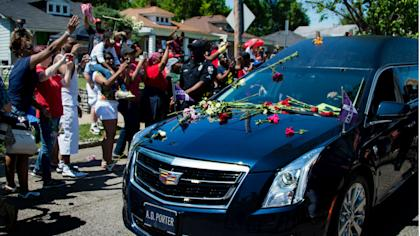 Mourners threw roses on Muhammad Ali's hearse on Friday as the funeral procession progressed in Louisville. (AP)