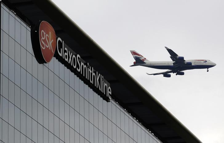 A British Airways airplane flies past a signage for pharmaceutical giant GlaxoSmithKlein in London