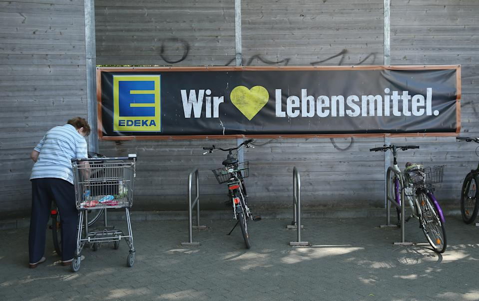 BERLIN, GERMANY - MAY 10:  An elderly woman loads her purchases into a bicycle basket outside an Edeka supermarket branch on May 10, 2016 in Berlin, Germany. German anti-cartel authorities announced yesterday they are charging Edeka as well as chains Metro, Netto and Rewe with price fixing of the three brands Beck's, Franziskaner and Hasseroeder with the beer companies' parent, Anheuser-Busch.  (Photo by Sean Gallup/Getty Images)