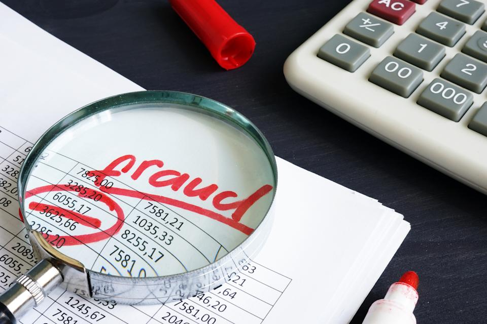 Financial or taxes fraud. Business report and magnifying glass.