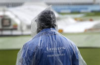 A steward wears a rain cape as he waits, as rain delays the start of play on the third day of the Test match between England and New Zealand at Lord's cricket ground in London, Friday, June 4, 2021. (AP Photo/Kirsty Wigglesworth)