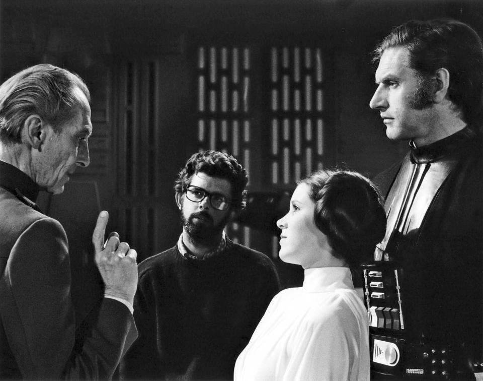 British actors Peter Cushing, David Prowse and American Actress Carrie Fisher with director, screenwriter and producer George Lucas on the set of his movie Star Wars: Episode IV - A New Hope. (Photo by Sunset Boulevard/Corbis via Getty Images)