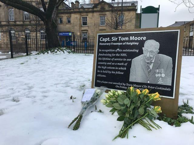 Tributes at the plaque in Town Hall Square, Keighley in tribute to 100-year-old charity fundraiser Captain Sir Tom Moore who died on Tuesday after testing positive for Covid-19