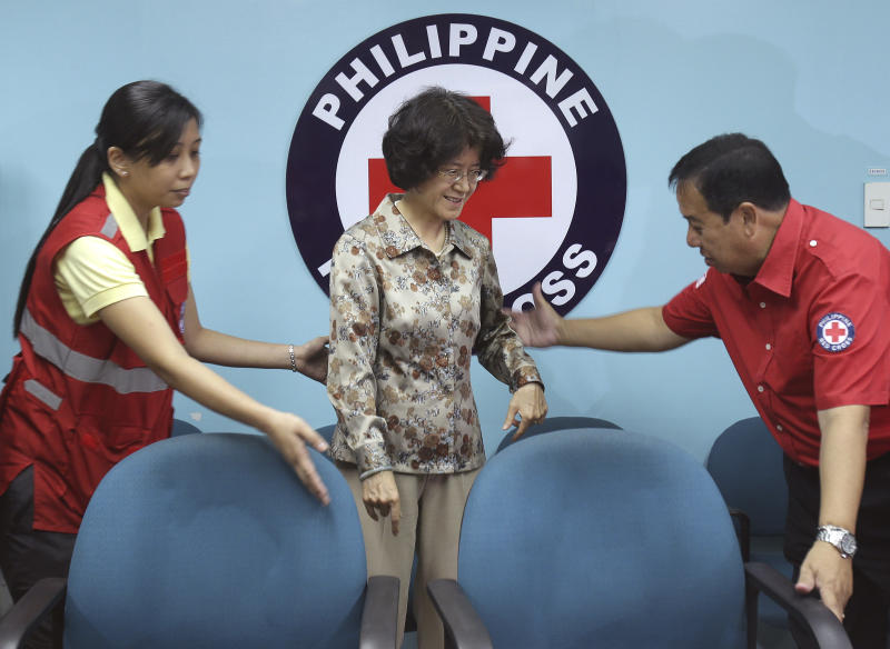 Philippine Red Cross Chairman Richard Gordon, right, welcomes Chinese Ambassador Ma Keqing, center, before turnover rites of payloaders donated by Chinese companies in Manila, Philippines on Monday, Dec. 2, 2013. China's envoy to the Philippines says it is the sovereign right of her country to establish a new maritime air defense zone over the East China Sea and replicate the move over another disputed region. (AP Photo/Aaron Favila)