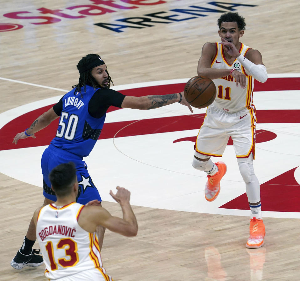 Orlando Magic guard Cole Anthony (50) defends Atlanta Hawks guard Trae Young (11) as he passes to teammate Bogdan Bogdanovic (13) in the second half of an NBA basketball game Thursday, May 13, 2021 in Atlanta. The Hawks defeated the Magic 116-93. (AP Photo/Tami Chappel)