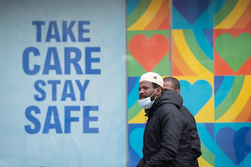 Residents wearing masks walk past a mural reading 'take care, stay safe' in Leicester this week (PA)